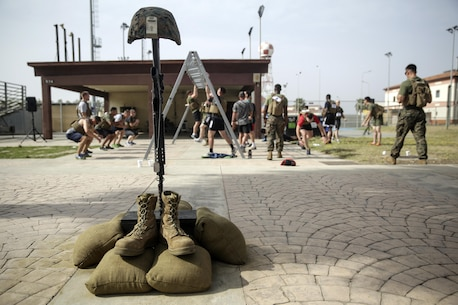 A tribute memorial to fallen service members stands by the pull up bars as Marines with Special Purpose Marine Air-Ground Task Force Crisis Response-Africa complete the Memorial Day Murph challenge at Naval Air Station Sigonella, Italy, May 30, 2016.  Marines and sailors ran one mile, completed 100 pull-ups, 200 push-ups, 300 air squats and another 1-mile run, all while wearing a flak jacket.  (U.S. Marine Corps photo by Cpl. Alexander Mitchell/released)
