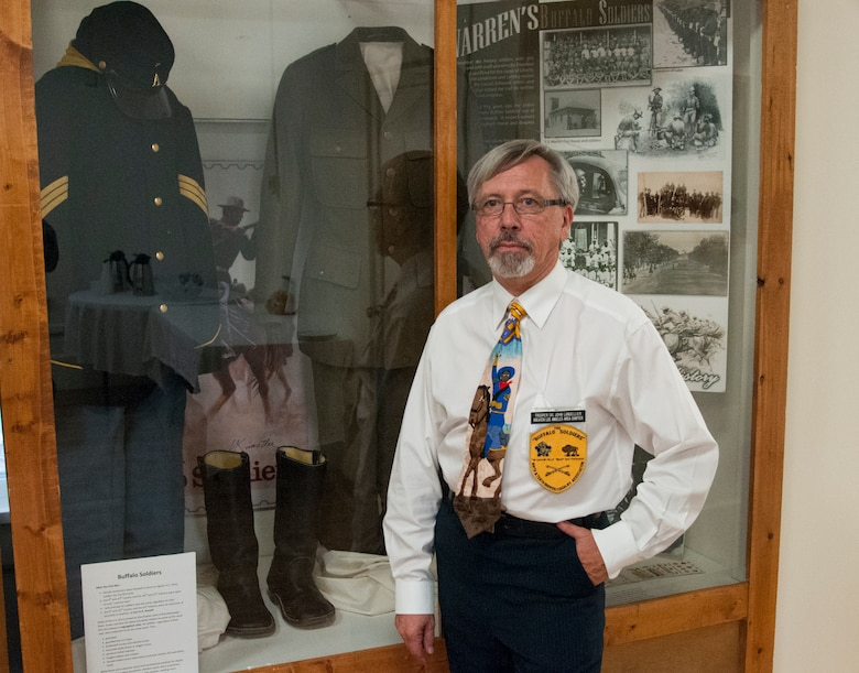 John Langellier, Ph.D., consulting historian, poses in the Warren ICBM & Heritage Museum on F.E. Warren Air Force Base, Wyo., June 1, 2016, in front of a display case housing Buffalo Soldier artifacts such as uniform items and photographs. (U.S. Air Force photo by Senior Airman Jason Wiese)