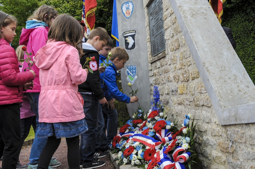 French children place flowers at the Currahee Memorial in Beuzeville au Plain, France.