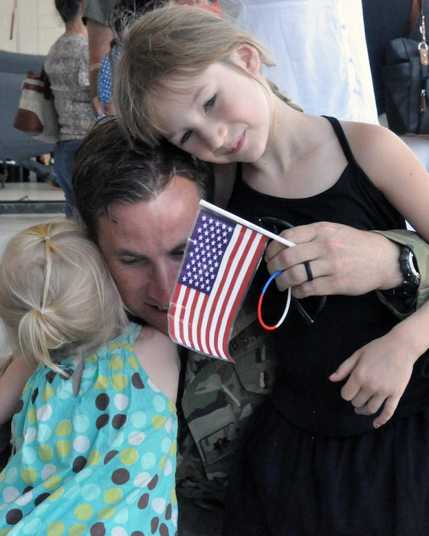 A combat rescue officer from the 306th Rescue Squadron hugs his daughters upon his return to Davis-Monthan Air Force Base, Ariz., from the Horn of Africa June 2. The 306th RQS is part of the 943rd Rescue Group, the Air Force Reserve Command's premier combat search and rescue group. They were deployed for four months and saved six lives during the deployment, flew more than 500 combat hours, conducted 67 parachute deployments, and provided more than 2,600 hours of dedicated alert coverage. (U.S. Air Force photo/Master Sgt. Greg Gaunt)