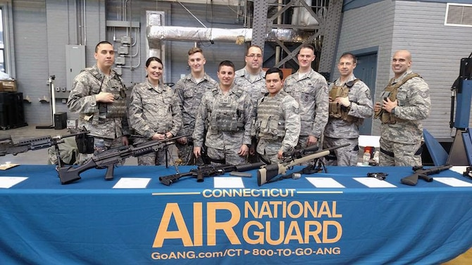Tech. Sgt. Marvin Perez, Staff Sgt. Monica Cox, Staff Sgt. Brandon Gasiorek, Tech. Sgt. Cody Remy, Senior Master Sgt. Chris Divita, Tech. Sgt. Noah Castro, Staff Sgt. Brian Davies, Master Sgt. Aaron Bowman, and Tech. Sgt. Nick Augelli stand at a weapons display table during a job fair held at the Hartford Armory in Conn. Feb. 27, 2016. (Photo courtesy of Master Sgt. Liz Toth)