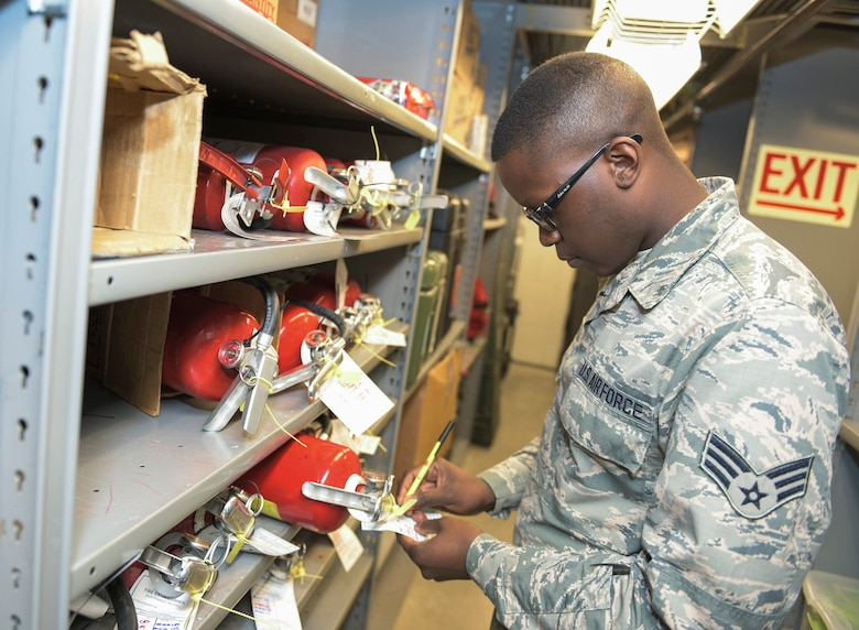 U.S. Air Force Senior Airman Cailin P. Scott, a material management specialist with the 264th Combat Communications Squadron, Illinois Air National Guard, examines fire extinguisher inspection dates in Peoria, Ill., April 30, 2016. Scott, who traces heritage to Africa, France, and India, said he believes diversity in the military promotes openness and the sharing of ideas. (U.S. Air National Guard photo by Staff Sgt. Lealan Buehrer)