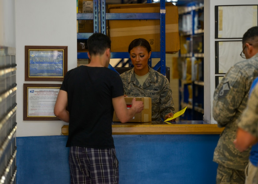 Airman Tazesha Wilson, 51st Communications Squadron postal clerk, delivers a package to a customer at Osan Air Base, Republic of Korea, June 3, 2016. The postal clerks verify the identities of customers before providing them with inbound packages. (U.S. Air Force photo by Senior Airman Victor J. Caputo/Released)
