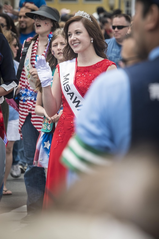 U.S. Air Force Senior Airman Taryn Mendoza, the 28th Annual American Day queen and an allergy and immunization technicians with the 35th Medical Operations Squadron, smiles and waves as she walks by attendees during the parade in Misawa City, Japan, June 5, 2016. More than 80,000 attendees from across the Aomori Prefecture traveled to Misawa City to enjoy American and Japanese culture. Serving as the American Day queen is a two-year honor requiring applicants to compete in numerous events testing their merit and propensity as a queen. Mendoza said she's truly humbled to have been a part of the event. She hails from Pocatello, Idaho. (U.S. Air Force photo by Staff Sgt. Benjamin W. Stratton)