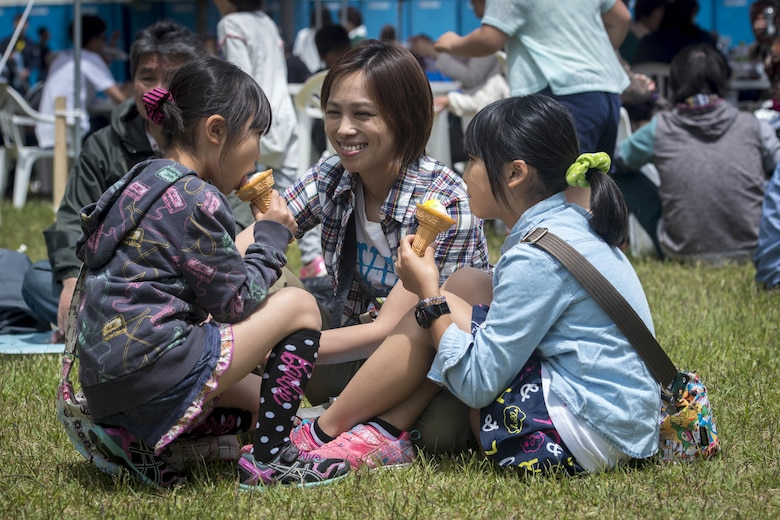 A Japanese mother and her two daughters enjoy ice cream cones during the 28th Annual American Day in Misawa City, Japan, June 5, 2016. Showcasing the region's bilateral partnership among U.S. military and Japanese residents, more than 80,000 annual attendees interacted with volunteers from private base organizations at various American-based food booths sharing a taste of home. Americans and Japanese residents also participated in activities such as a family fun run, an American-themed parade, sports tournaments, street performances and a haunted house. (U.S. Air Force photo by Staff Sgt. Benjamin W. Stratton)