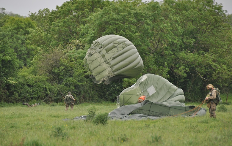 Members of the Round Canopy Parachuting Team, dressed in D-Day period costumes, parachuted into Fresville, France June 2, 2016 during an exhibition jump.  The Round Canopy Parachuting Team invited members of the 815th Airlift Squadron to assist in the drop zone.  More than 380 service members from Europe and affiliated D-Day historical units are participating in the 72nd anniversary as a part of Joint Task Force D-Day 72.  The Task Force, based in Sainte-Mère-Église, France, is supporting local events across Normandy, from May 30 - 6 June, 2016 to commemorate the selfless actions by all of the allies on D-Day that continue to resonate 72 years later.  (U.S. Air Force photo by Master Sgt. Jessica L. Kendziorek)