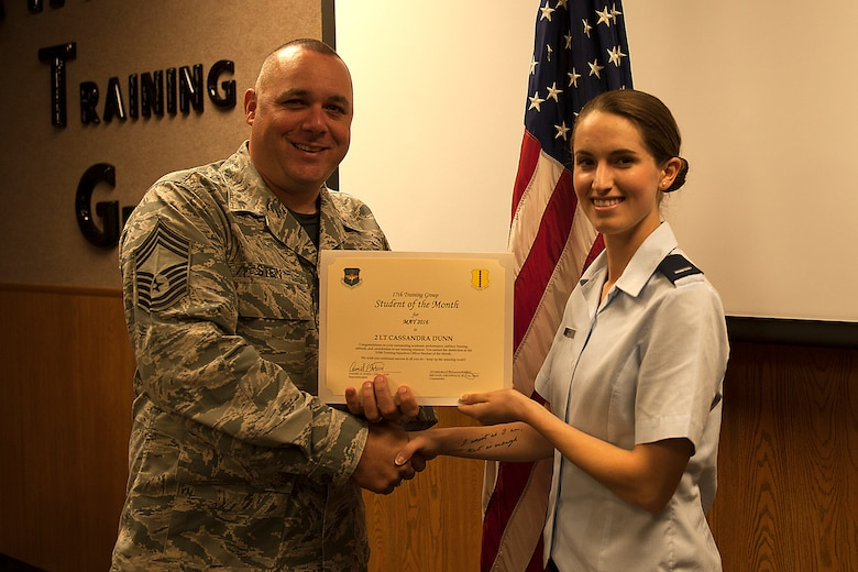 U.S. Air Force Chief Master Sgt. Daniel Stein, 17th Training Group superintendent, presents the 315th Training Squadron Officer Student of the Month award for May 2016 to 1st Lt. Cassandra Dunn in Brandenburg Hall on Goodfellow Air Force Base, Texas, June 3, 2016. (U.S. Air Force photo by Airman 1st Class Caelynn Ferguson/Released)