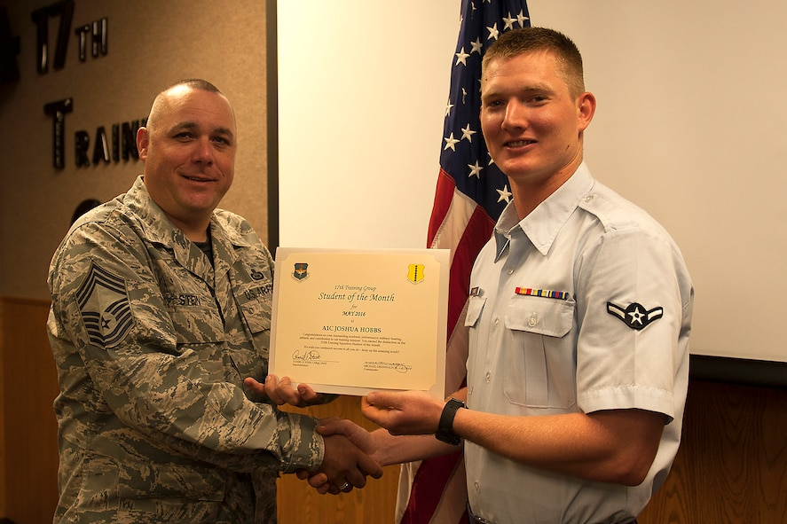 U.S. Air Force Chief Master Sgt. Daniel Stein, 17th Training Group superintendent, presents the 312th Training Squadron Student of the Month award for May 2016 to Airman 1st Class Joshua Hobbs in Brandenburg Hall on Goodfellow Air Force Base, Texas, June 3, 2016. (U.S. Air Force photo by Airman 1st Class Caelynn Ferguson/Released)