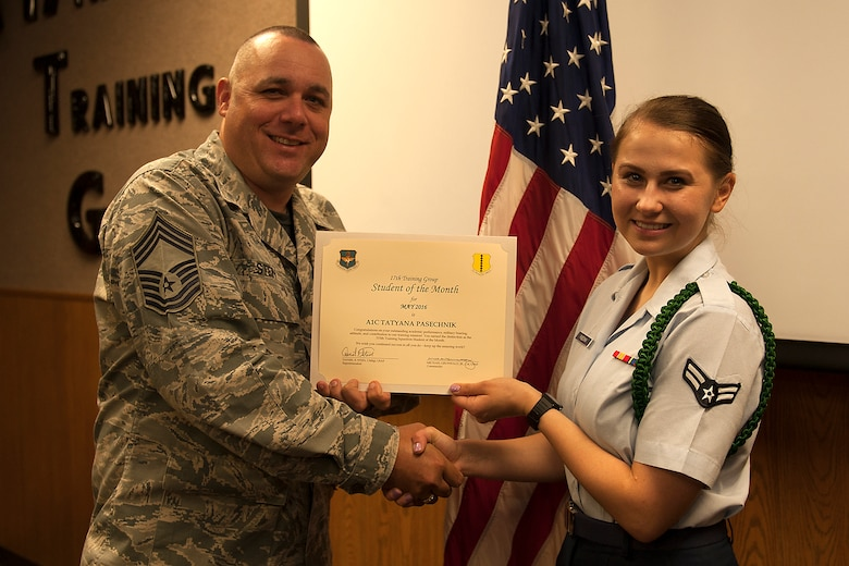 U.S. Air Force Chief Master Sgt. Daniel Stein, 17th Training Group superintendent, presents the 315th Training Squadron Enlisted Student of the Month award for May 2016 to Airman 1st Class Tatyana Pasechnik in Brandenburg Hall on Goodfellow Air Force Base, Texas, June 3, 2016. (U.S. Air Force photo by Airman 1st Class Caelynn Ferguson/Released)