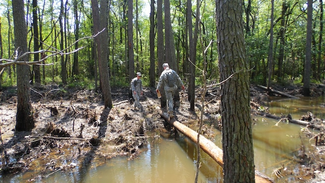 Soldiers assigned to the U.S. Army Reserve Command Augmentation Unit (UAU) cross a water obstacle while attempting to locate one of several points for a land navigation and orienteering exercise during their Battle Assembly on June 4, 2016, at Fort Bragg, N.C. The training involved movement to the training are via U.S. Army Reserve UH-60 Black Hawk helicopters then navigating to fixed points using a map, compass and protractor. The mission of the UAU is to augment United States Army Reserve Command staff during exercises, crisis actions, or a presidential selective reserve call-up. Soldiers of the UAU train regularly to provide the most qualified, trained, and prepared Soldiers upon request by Army units. (U.S. Army Reserve photo by Lt. Col. Kristian Sorensen/released)