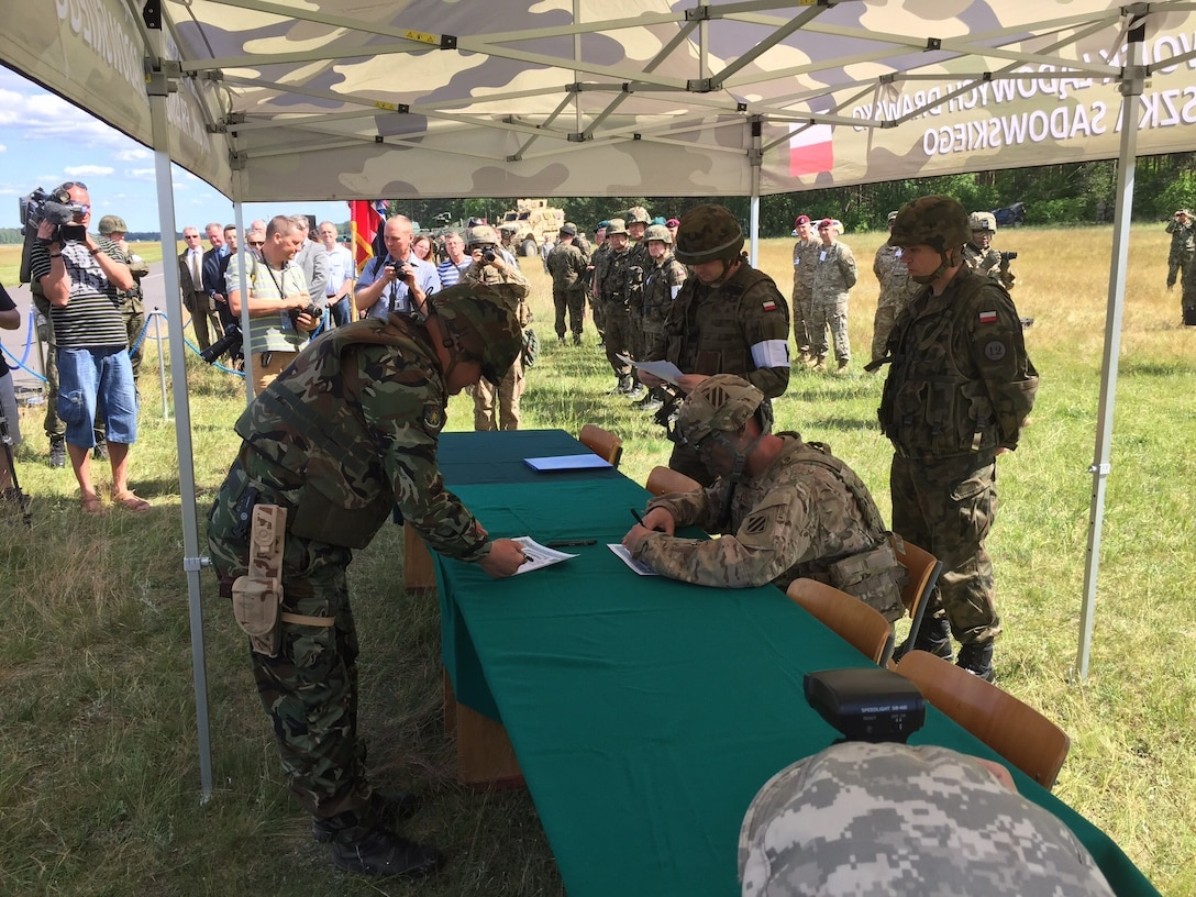 U.S. Army Col. Phil Brooks, seated, commander of the 1st Armored Brigade Combat Team, 3d Infantry Division, Fort Stewart, Ga., signs a transfer of authority agreement during an opening ceremony for Exercise Anakonda 2016 at the Drawsko Pomorskie Training Area, Poland, June 6. Exercise Anakonda 2016 is a Polish-led, joint multinational exercise taking place throughout Poland June 7-17. The exercise involves approximately 31,000 participants from more than 20 nations. Exercise Anakonda 2016 is a premier training event for U.S. Army Europe and participating nations and demonstrates the United States and partner nations can effectively unite under a unified command while training on a contemporary scenario. (U.S. Army photo by Timothy L. Hale) (Released)