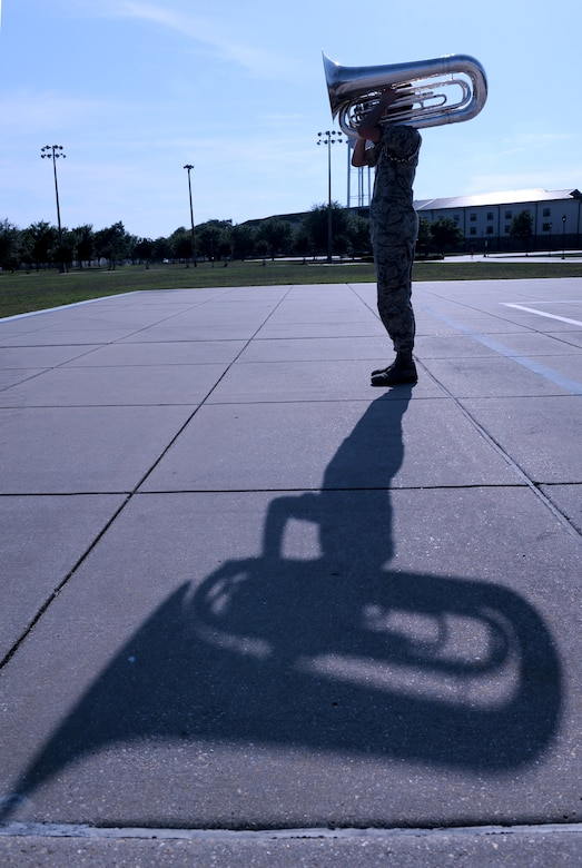 Airman 1st Class Nicolas Overton, 81st Training Wing Drum and Bugle Corps tuba player, plays a musical piece during a practice session on the drill pad at the Levitow Training Support Facility May 31, 2016, Keesler Air Force Base, Miss. The drum and bugle corps performs at various events such as 81st Training Group student parades and drill downs in addition to attending Air Force specialty code technical training on a daily basis. (U.S. Air Force photo by Kemberly Groue)