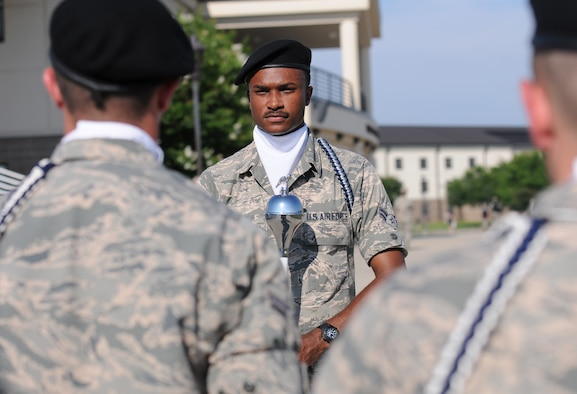 Airman 1st Class Evan Mack, 81st Training Wing Drum and Bugle Corps drum major, leads the band onto the drill pad at the Levitow Training Support Facility during a practice session May 31, 2016, Keesler Air Force Base, Miss. The drum and bugle corps performs at various events such as 81st Training Group student parades and drill downs in addition to attending Air Force specialty code technical training on a daily basis. (U.S. Air Force photo by Kemberly Groue)
