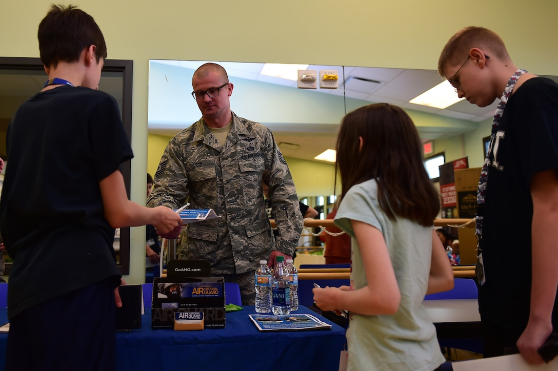 Tech. Sgt. Brian Lilly, Colorado Air National Guard 140th Wing recruiter, speaks with children June 3, 2016, during a College and Career Expo at the youth center on Buckley AFB, Colo. Members from the ANG spoke with Buckley AFB youth, along with providing informational pamphlets, about the educational and career benefits that the Guard offers. (U.S. Air Force photo by Airman 1st Class Gabrielle Spradling/Released)