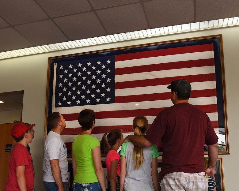 Master Sgt. Kelly K. Collett, broadcast manager, thrid from left, and his family take a tour of the TEC TV studios June 6, 2016, at the I.G. Brown Training and Education Center in Louisville, Tenn., to include the American flag display in Spruance Hall. The flag was last flown on campus July 29, 1986, after a 16-year journey over the capitols of every state and territory in the United States. (U.S. Air National Guard  photo by Master sgt. Mike R. Smith/released)