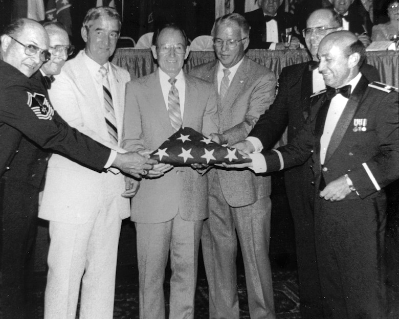 From left, Chief Master Sgt. Myron Pigg, Senior Master Sgt. Jimmie Stewart, Chief Master Sgt. Jim Laux, Chief Master Sgt. Paul Lankford, Col. Edmund Morrisey, Chief Master Sgt. Gordon Kniskern, and Col. Larry Martin commemorate the return of the American flag, July 24, 1986, at the I.G. Brown Training and Education Center in Louisville, Tenn., nearly 16 years to the month after it was sent out by NCO academy class 71-1 to fly over every state and territory of the United States. The flag was last flown July 29, 1986, at the first reveille of NCO academy class 86-3. Thousands of Airmen have seen the flag on display in Spruance Hall during the 30 years since. (U.S. Air National Guard file photo/released)