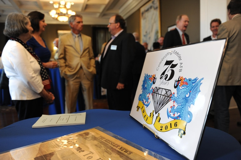 "The 75th anniversary logo sits on a table at Keesler's 75th Anniversary Historical Display Unveiling at the Biloxi Visitors Center June 3, 2016, Biloxi, Miss. A display featuring 14 historical panels created by Keesler personnel was unveiled along with the newest 75th anniversary logo. Additionally, Biloxi Mayor Andrew 'FoFo' Gilich read the ""Biloxi/Keesler Partnership Day"" proclamation at the event. (U.S. Air Force photo by Kemberly Groue)"