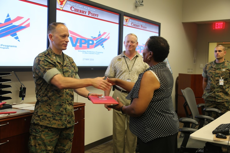 Col. Chris C. Pappas III awards departments during a Voluntary Protection Program Gold status achievement ceremony at Marine Corps Air Station Cherry Point, N.C., May 27, 2016. Six departments were among the first to achieve Gold status within MCAS Cherry Point VPP. Gold status is achieved when all safety protocols implemented by the VPP are completed and maintained. Some of those requirements involve monthly supervisor inspections, achieving 90-percent medical surveillance or higher, completing VPP passports and completing Occupational Safety and Health Administration training. Pappas is the air station commanding officer.  (U.S. Marine Corps photo by Cpl. N.W. Huertas/ Released)