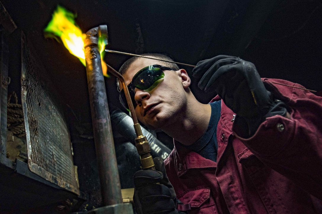 Navy Petty Officer 2nd Class Jonathan Allen brazes together metal fittings in the pipe shop aboard the USS Dwight D. Eisenhower in the Atlantic Ocean, June 6, 2016. The ship is supporting maritime security operations in the areas of responsibility for the U.S. 5th and 6th fleets. Navy photo by Petty Officer 3rd Class Anderson W. Branch
