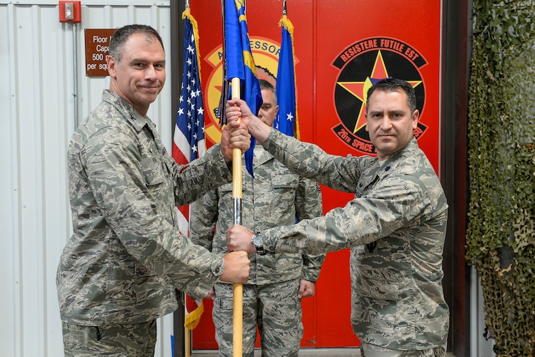 Col. Gary Rose, 57th Adversary Tactics Group commander, presents the guidon to Lt. Col. Anibal Rodriguez during the 527th Space Aggressors Squadron's change of command at Schriever Air Force Base, Colorado, Thursday, June 2, 2016. Rodriguez assumes the 527 SAS command from Lt. Col. Kyle Pumroy. (U.S. Air Force photo/Christopher DeWitt)