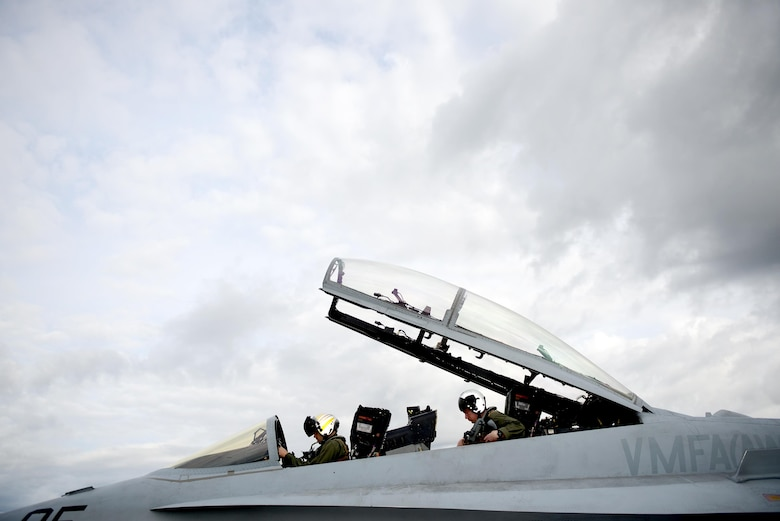 U.S. Marine Corps F-18 Hornet pilots assigned to Fixed Marine All-Weather Fighter Attack Squadron 242, Marine Corps Air Station Iwakuni, Japan, secure themselves inside their cockpit June 7, 2016, during RED FLAG-Alaska (RF-A)16-2, at Eielson Air Force Base, Alaska. Pilots involved with RF-A are exposed to realistic combat training supported by the 18th Aggressor Squadron, which shares knowledge of flying and provides the best air combat training possible. (U.S. Air Force photo by Tech. Sgt. Steven R. Doty)