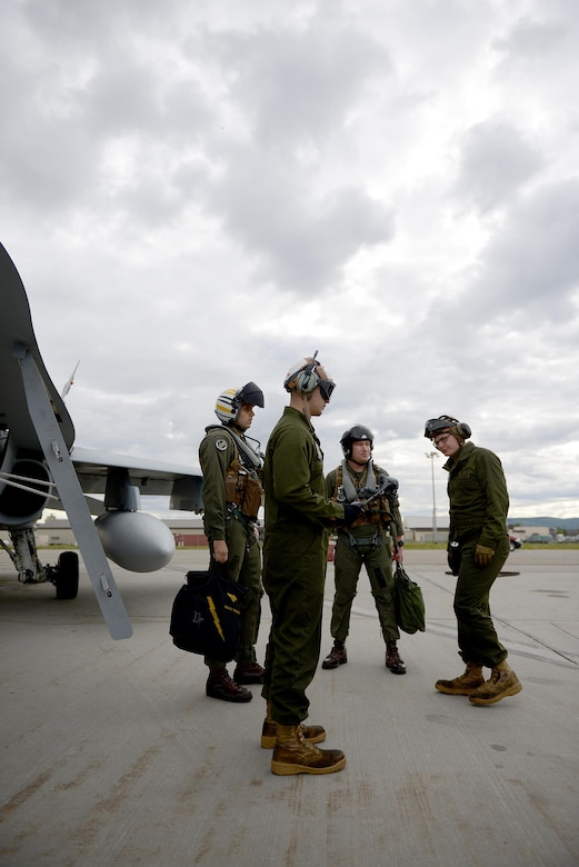 U.S. Marine Corps Cpl. Austin Perry, front center, an F-18 Hornet powerline mechanic and plane captain assigned to Fixed Marine All-Weather Fighter Attack Squadron (VMFA (AW)) 242, Marine Corps Air Station Iwakuni, Japan, communicates with operations staff over the radio June 7, 2016, during RED FLAG-Alaska (RF-A) 16-2, at Eielson Air Force Base, Alaska. VFMA (AW) is one of more than 30 units participating in RF-A 16-2 that benefits from the unique opportunity to integrate with various joint, coalition and multilateral forces to train at a simulated forward operating base. (U.S. Air Force photo by Tech. Sgt. Steven R. Doty)