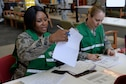 U.S. Air Force Master Sgt. Ukeia Carter, 36th Medical Support Squadron superintendent, left, and Tech. Sgt. Gretchen Hopper, 36th MDSS TRICARE operations and patient administration flight NCO in charge, check in patients during a typhoon recovery exercise June 6, 2016, at Andersen Air Force Base, Guam. The 36th Medical Group performed typhoon recovery response, to include flu o-utbreak mitigation, assessment of injured personnel and providing aid to large numbers of patients at one time. (U.S. Air Force photo by Airman 1st Class Alexa Ann Henderson/Released)