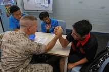 1st Lt. Joseph C. Wright arm wrestles a student at Sanderson Middle School, Northern Territory, Australia, on June 3, 2016. Marines with the Forward Coordination Element, Marine Rotational Force – Darwin, helped with an English oral language class by talking, playing and listening to middle school students. Wright, from Bogata, Texas, is a communications officer with FCE, MRF-D.