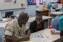 Sgt. Samuel T. Gbatu converses with a student at Sanderson Middle School, Northern Territory, Australia, on June 3, 2016. Marines with the Forward Coordination Element, Marine Rotational Force – Darwin, helped with an English oral language class by talking, playing and listening to middle school students. Gbatu, from Brooklyn Park, Minnesota, is an administrative specialist with FCE, MRF-D.