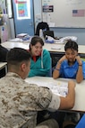 Lance Cpl. Simon B. Delacruz Jr. plays a board game with students at Sanderson Middle School, Northern Territory, Australia, on June 3, 2016. Marines with the Forward Coordination Element, Marine Rotational Force – Darwin, helped with an English oral language class by talking, playing and listening to middle school students. Delacruz, from Rochester, New York, is a cyber network operator with FCE, MRF-D.