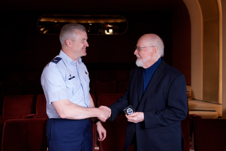 Col. Larry Lang, presents a band challenge coin to legendary conductor and composer John Williams at the conclusion of a recent interview with the former Airmen. Williams served in the U.S. Air Force as a pianist and brass player and also wrote and arranged as a secondary duty. (U.S. Air Force Photo/CMSgt Bob Kamholz)