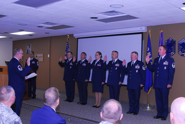 Senior Master Sgt. Bill Shirley, superintendent of inspections, inducts six of the newest master sergeants in the 120th Airlift Wing Larsen room, June 4, 2016. Attaining the rank of master sergeant allows the members to be a part of an elite group called the Top 3. (U.S. Air National Guard photo by Staff Sgt. Lindsey Soulsby/Released)