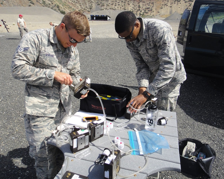 "Airman 1st Class Ants Vahk and Airman Antione Van, both 92nd Aerospace Medicine Squadron bioenvironmental engineers, prepare air sampling pumps May 25, 2016 at the Grand Coulee Damn shooting range. The air samples collected were of copper dust, fumes and lead during a heavy weapons firing. ""We'll do an air sampling, send the samples to the lab and then wait for the results to let us know if we need to take any further precautions,"" Vahk said.  (Courtesy Photo)"