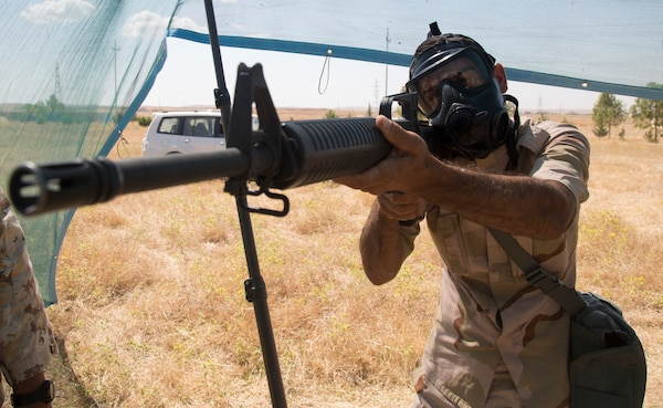 A Peshmerga soldier practices aiming down his sights while wearing a chemical protective mask during a chemical, biological, radiological, and nuclear class at a base near Erbil, Iraq, May 25, 2016. As part of a 10-week basic infantry course, CBRN training is provided to Peshmerga soldiers to aid in the fight against ISIL.  (Army Photo by Spc. Jaquan P. Turnbow)