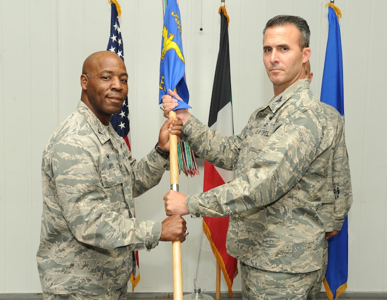 Col. Zachary Zeiner assumes command of the 387th Air Expeditionary Group and receives the guidon from Col. Clarence Lukes Jr., 386th Air Expeditionary Wing commander, during a change of command ceremony at an undisclosed location in Southwest Asia, June 7, 2016. Prior to assuming command of the 387 AEG, Zeiner served as the Deputy Command Center Director for U.S. Northern Command at Peterson Air Force Base, Colo. Zeiner will be responsible for a group that provides support for base operations, coordination with host nation partners, and administration of the Joint Expeditionary Tasked individual augmentees in the area of responsibility. (U.S. Air Force photo by Senior Airman Zachary Kee)