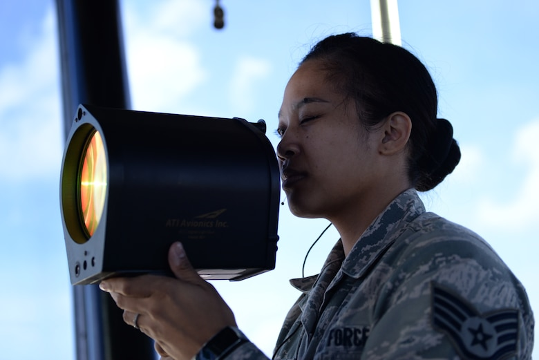 Staff Sgt. Tiffany Degracia, 36th Operations Support Squadron air traffic controller, signals a vehicle on the flightline with a light gun June 2, 2016, at Andersen Air Force Base, Guam. The light guns flash red, white or green lights in various patterns to signal how to proceed when communication with an aircraft or vehicle is lost. (U.S. Air Force photo by Airman 1st Class Jacob Skovo)