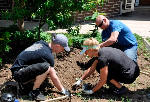 425th Air Base Squadron members plant flowers and vegetables at a local girls' care and rehabilitation center garden as part of a landscaping project May 7, 2016.