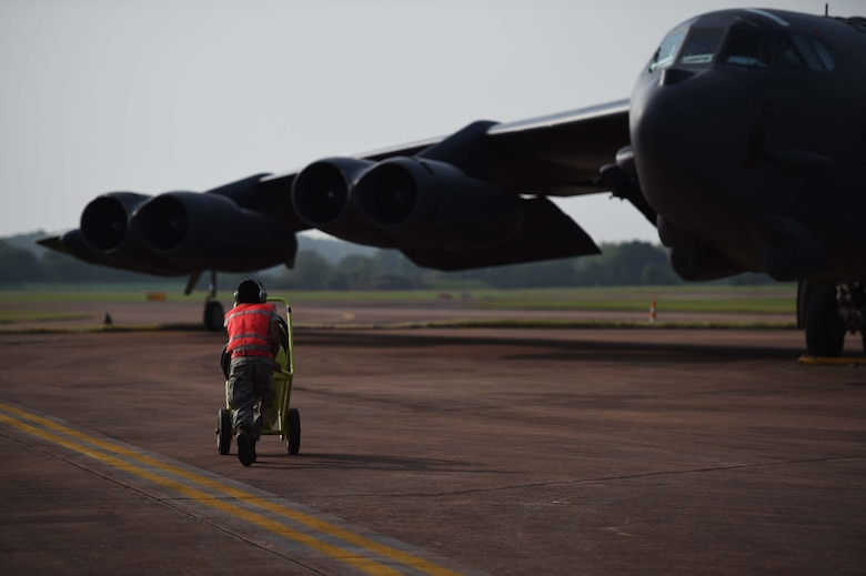 A maintenance Airman from Minot Air Force Base, N.D., runs to a B-52H Stratofortress as it parks on RAF Fairford, United Kingdom, June 7, 2016, after flying a training sortie in support of exercise BALTOPS 16. The mission trained the aircrew on air interdiction and interoperability with sister services and partner nations. (U.S. Air Force photo by Airman 1st Class Zachary Bumpus)