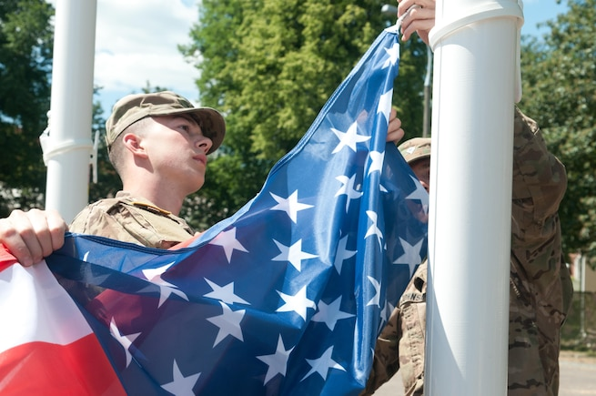 Pvt. 1st Class Austin Thompson, from Minford, Ohio, and Spc. Eric M. Johnson from Los Angeles, Ca., with the 554th Military Police Company from Stuttgart, Germany, raise the American flag for the opening ceremony of Exercise Anakonda 2016.