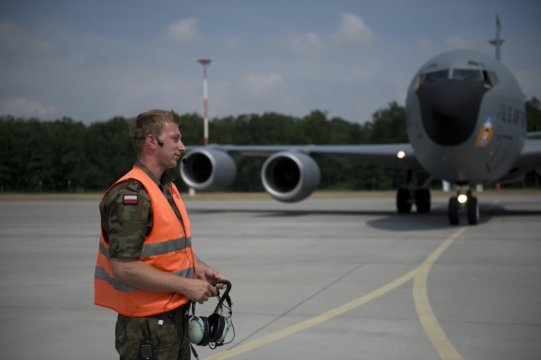 A Polish air force service member removes his headset after marshaling a KC-135 from the 100th Air Refueling Wing, England, in preparation for exercise Baltic Operations 2016 at Powidz Air Base, Poland, June 2, 2016. Fifteen NATO and two partner nations will participate in the 44th iteration of the multinational maritime exercise BALTOPS 2016 in Estonia, Finland, Germany, Poland, Sweden, and throughout the Baltic Sea, June 3-19, 2016. (U.S. Air Force photo by Senior Airman Erin Babis/Released)