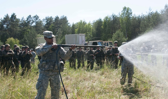 Spc. Frank Gully, a Chemical Operations Specialist, from the 44th Chemical Battalion of the Illinois National Guard, demonstrates his unit's equipment to Polish Soldiers, from the 5th Chemical Regiment, during Exercise Anakonda 2016, a Polish-led, multinational exercise running from June 7-17. (U.S. Army photo by Spc. Miguel Alvarez/ Released)
