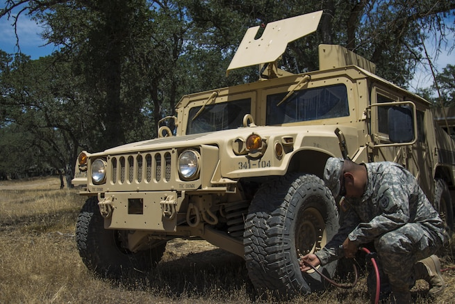 Pvt. Daniel Harrison, 341st Military Police Company, checks and refills air in vehicle tires during the Combat Support Training Exercise, Fort Hunter Liggett, Calif., June 6, 2016. The purpose of the CSTX is for Army Reserve units to practice their technical skills in a tactical environment under combat-like conditions.  (US Army photo by Cpl. Timothy Yao, 311th Sustainment Command (Expeditionary)/Released)