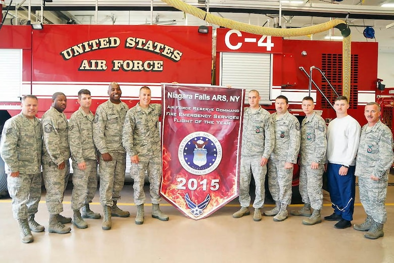 Members of the 914th Airlift Wing Fire Flight pose with the banner for the Air Force Reserve Command Fire Emergency Services of the Year on June 5, 2016 at Niagara Falls Air Reserve Station. The flight beat 26 other units to attain the honor. (U.S. Air Force photo by Staff Sgt. Richard Mekkri/released)