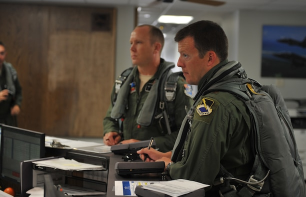 Maj. Justin Hedrick, 2nd Fighter Training Squadron pilot, receives a brief before stepping to his aircraft for a mission June 1, 2016, at the 2nd FTS building. The 2nd FTS is tasked with going head-to-head with the F-22 Raptor, providing world class, professional air-to-air threat replication.
