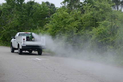 "Mitch Burcham, 633rd Civil Engineer Squadron Entomology flight pest controller, drives a truck with a fog machine marked ""Contaminated with Pesticides,"" to eradicate the mosquito populations at Langley Air Force Base, Va., June 6, 2016. Pest controllers will fog three nights each week from 7 p.m. to approximately 11 p.m., provided the weather permits, through Bethel housing, housing on Langley Air Force Base, followed by the industrial and office buildings across the installation. (U.S. Air Force photo by Staff Sgt. Teresa J. Cleveland)"