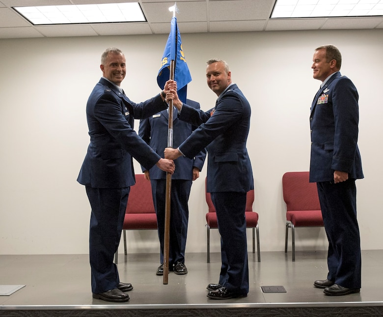 Colorado Air National Guard Col. Brian D. Turner, commander, 140th Operations Group, presents the guidon to Lt. Col. Jeremiah S. Tucker as he assumes command of the 140th Operations Support Squadron (OSS),  June 5, 2016, Buckley Air Force Base, Aurora, Colo. The 140 OSS was previously under the command of Lt. Col. Scott D. Van Beek (right), special projects officer, 140 Wing Plans.  (U.S. Air National Guard photo by Staff Sgt. Michelle Y. Alvarez-Rea)