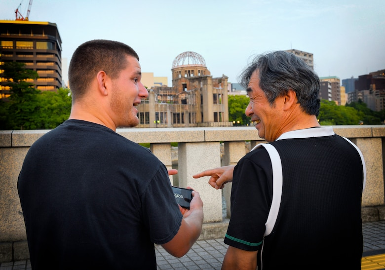 Joseph Galloway, 730th Air Mobility Squadron jet propulsion technician, discusses Japanese drift tracks with Fumio, Nissan 180sx owner, in front of the Hiroshima Peace Memorial at Hiroshima, Japan, May 31, 2016. Despite the fact that there are Japanese living today who experienced World War II, many Japanese and Americans advocate continuing peace and friendship between Japan and the U.S. (U.S. Air Force photo by Airman 1st Class Elizabeth Baker/Released)