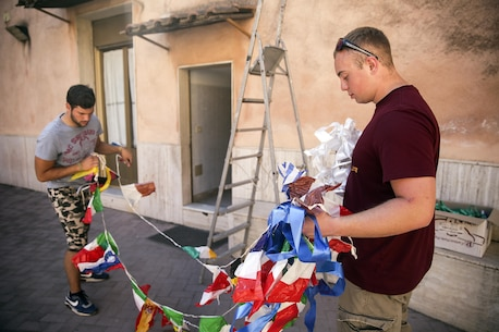 RPSA Alexander Varner, a religious personnel specialist with Special Purpose Marine Air-Ground Task Force Crisis Response-Africa, helps an employee at Marie Ausiliatrice School hang a banner in Catania, Italy, June 7, 2016.  Marines volunteered their time performing general site maintenance and building an above ground pool in preparation for a summer camp at the orphanage.  (U.S. Marine Corps photo by Cpl. Alexander Mitchell/released)