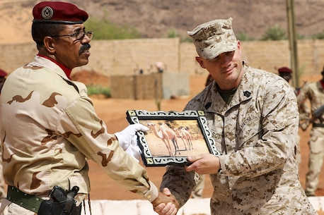 Sgt. Maj. Daniel Wilson, Sergeant Major of the Logistics Combat Element for Special Purpose Marine Air-Ground Task Force Crisis Response-Africa, recieves a gift from the Mauritanian Groupement Special d'Intervention in Mauritania, June 3, 2016.  Marines facilitated security force assistance in support of the Mauritanian GSI counter-terrorism efforts by assessing and conducting advance infantry training, tactical convoy operations, vehicle operations, medical, and communications training.  (U.S. Marine Corps courtesy photo/released)