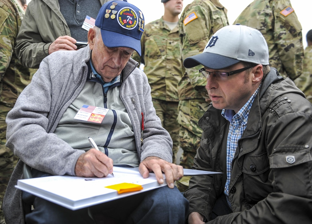 Cliff Goodall, a World War II veteran, signs an autograph after a memorial ceremony June 4, 2016, in Angoville-au-Plain, France. The memorial ceremony was in honor of Kenneth Moore and Robert Wright, medics with the 101st Airborne Division during World War II, who provided medical care to allies and enemies alike at the Angoville-au-Plain church in June 1944. (U.S. Air Force photo by Staff Sgt. Timothy Moore)